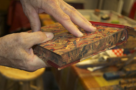 Dan holding a edge marbled book. Photo by Maggie Holtzberg