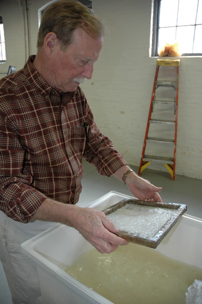 Peter Hopkins lifting a screen with pulp on it