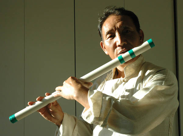 Penpa Tsering playing one of his handmade flutes. Photo by Maggie Holtzberg