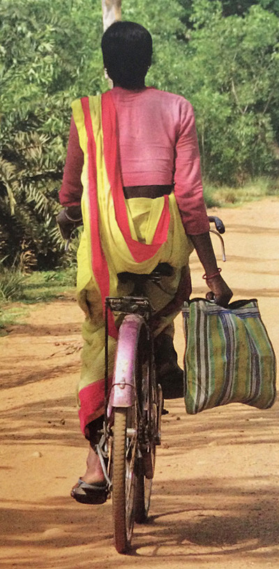 Woman riding a bicyle wearing a sari. Photo from Saris: Tradition and Beyond by 	Rta Kapur Chishti