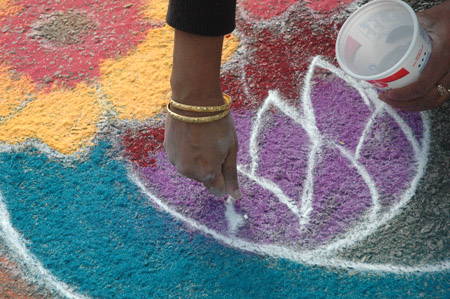 Close-up of Sridevi making kolam