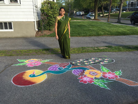 Srivdevi Karthikeyan posing with her finished kolam featuring two peacocks.